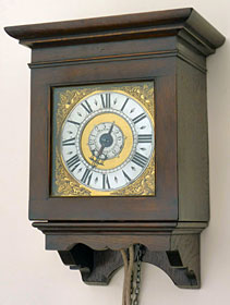 A tiny oak, single-handed, hooded wall clock dating from the early eighteenth century